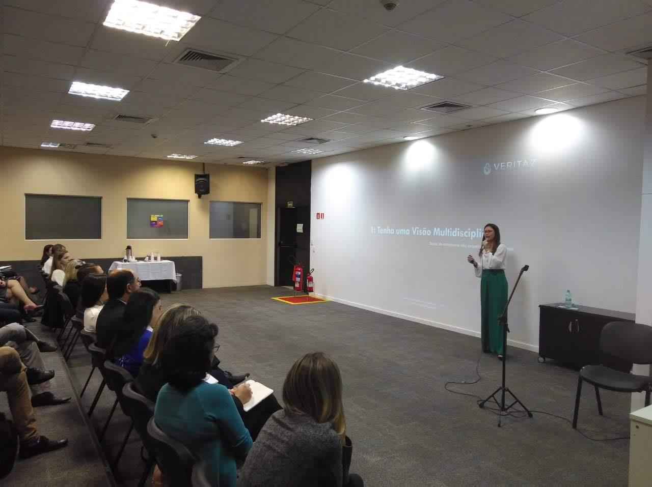 Letícia Sugai à frente do palco palestrando para convidados